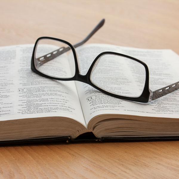 Open Bible with glasses sitting on top of it.